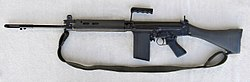 A black FN FAL battle rifle lain on a grey background, pointing to the viewer's left