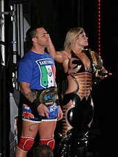 A man and a woman pose together. The dark-haired man is standing on the left and is wearing a blue T-shirt with the Italian flag and the word 'Santino' written upon it, blue wrestling tights, and red kneepads. He is wearing a gold wrestling championship around his waist. The blond haired woman is standing on the right, wearing a black catsuit with the sides of the torso removed to bare part of her midriff. She is holding a wrestling championship upon her left shoulder and has her right arm outstretched.