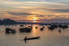 Silhouette of a fisherman on his pirogue at sunrise in Si Phan Don Laos.jpg