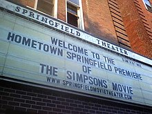 "A board reads ""Welcome to the Hometown Springfield Premiere of The Simpsons Movie"