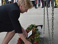 Catherine Ebert-Gray, United States Ambassador to the Solomon Islands, is pictured in a color photograph laying a wreath at the Munro memorial at the Point Cruz Yacht Club in 2017