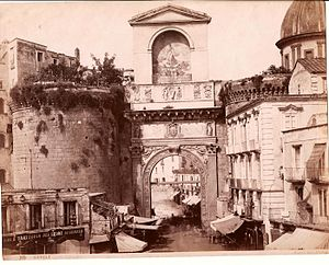 Porta Capuana - 19th century photograph - the top level has since been removed. The dome of Santa Caterina a Formiello is visible on right.