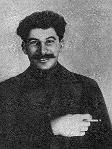 Foto von Stalin als jüngerer Mann, der in die Kamera lächelt und von der Hüfte aufwärts abgeschnitten ist