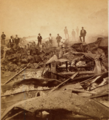 Stereograph showing men standing amid the ruins caused during the 1877 Pittsburgh railroad riots.png