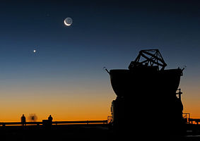 Astronomers enjoying the sunset at Paranal, on ESO's Very Large Telescope's platform, just before the beginning of their night-time observations. The dome of one of the VLT's Auxiliary Telescopes is seen in the foreground. The crescent Moon and, to its left, planet Venus, make for a beautiful scenery.