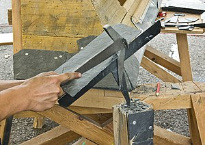 Slater - Cutting a slate with a slater's hammer on a slater's stake
