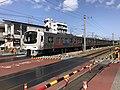 Train for Hainuzuka Station passing Sangyo University Crossing.jpg