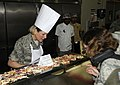 U.S. Air Force Col. Jennifer Fullmer, left, the vice commander of the 379th Air Expeditionary Wing, serves turkey to an Airman during a Thanksgiving Day meal in the dining facility at an undisclosed location 131128-F-QD538-032.jpg