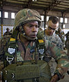 U.S. Army Pfc. Stephen Rathje, right, with Charlie Company, 1st Battalion, 325th Infantry Regiment, assists South African Army Capt. S. S. Tyali, with the 44th Parachute Regiment, with his parachute before 130723-A-FP002-001.jpg