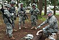 U.S. Army Sgt. Ian James, right, a health care specialist with Bravo Company, Madigan Army Medical Center, explains saline lock and intravenous fluids grading procedures during Expert Field Medical Badge 130404-A-FS521-207.jpg