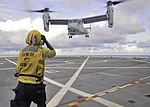 U.S. Navy Aviation Boatswain's Mate (Handling) 3rd Class Christopher Sewell directs a Marine Corps MV-22 Osprey tiltrotor aircraft as it takes off from the amphibious transport dock ship USS New York (LPD 21) 131205-N-YO707-750.jpg
