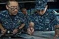 U.S. Navy Lt. j.g. McKinley Kim, left, and Quartermaster 1st Class David Heinonen plot the course of the amphibious dock landing ship USS Tortuga (LSD 46) April 23, 2013, in the U.S. 7th Fleet area 130423-N-IY633-101.jpg