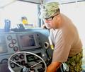 USCG technician providing routine maintenance to the bridge equipment of a patrol boat in Guantanamo.png