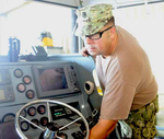 USCG technician providing routine maintenance to the bridge equipment of a patrol boat in Guantanamo.png