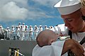 US Navy 060905-N-4965F-008 A new father holds his child for the first time after returning from a six-month deployment aboard the guided missile destroyer USS Russell (DDG 59).jpg