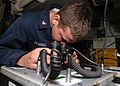 US Navy 070716-N-1994L-041 Aviation Electronics Technician 1st Class Russell Vaughn tests the light receiving ability while performing maintenance on a pair of night-vision goggles aboard amphibious assault ship USS Bonhomme Ri.jpg