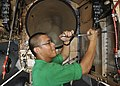 US Navy 100929-N-7103C-002 Aviation Structural Mechanic (Equipment) Airman Frederick Copuyoc removes bolts from the access panel of an F-A-18C Horn.jpg