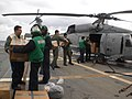 US Navy 110316-N-1447C-002 Sailors aboard the guided-missile destroyer USS Mustin (DDG 89) load food, clothing, blankets, hygiene products and othe.jpg