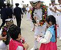 US Navy 110813-N-DB801-370 Capt. Charles Williams, U.S. 7th Fleet Chief of Staff, receives cupcakes from Korean children.jpg