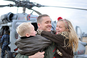 US Navy 111210-N-FU443-288 A Sailor hugs his son and daughter during the squadron's homecoming ceremony.jpg