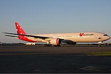 A Boeing 777-300ER in red and white livery with the Southern Cross painted on the tail. It is being parked on a sunny, cloudless day, facing right.