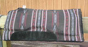 Saddle blanket - A modern western saddle pad, with blanket design on top, fleece underneath, and felt or foam padding on the inside