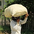 Woman carrying a bag of rice on head in Bohol 2.jpg