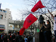 Three red flags with globe logos being held above a crowd of people.