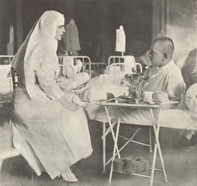 """Regina Maria pe timpul vizitei într-un spital în anul 1917. Imagine reprodusă din lucrarea """"Fotografii din Războiul pentru întregirea neamului 1916-1919"""" publicată în 1924 de Muzeul Militar Naţional din România. Sursă foto: wikipedia."""