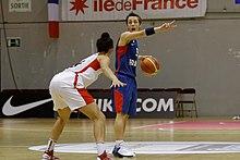En fransk spiller, bold i hånden, overfor en canadisk spiller.
