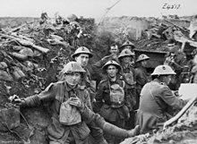 Men wearing military uniforms and helmets stand in a trench. Around them debris from battle is strewn