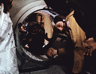 Space Race - Astronaut Thomas P. Stafford and cosmonaut Aleksei Leonov shake hands in space to ease Cold War tensions.