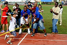 A Special Olympics (SO) athlete crosses the finish line after completing the last leg of a 400 meter relay race during the Kadena Air Base SO event in Okinawa, Japan, Nov 111105-F-FL863-002.jpg