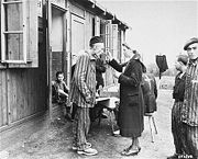 A sick Polish survivor in the Hannover-Ahlem concentration camp receives medicine from a German Red Cross worker