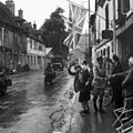A union flag hangs in the main street of Les Andelys in Normandy as British forces arrive, 31 August 1944. The woman in the foreground is Madame Scarlett, wife of an expatriate Englishman and owner of the Hotel des Fleu B9869.jpg