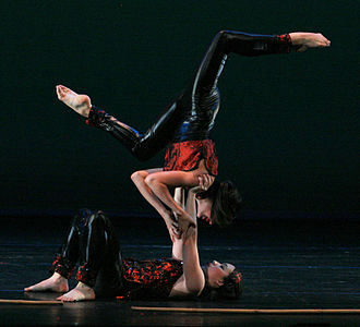 Acrobalance - Acro dancers perform a stag shoulder stand.