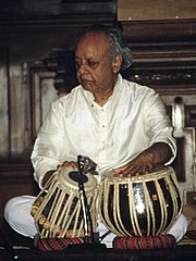 An old man sits cross-legged on the ground and rests his hands on two small drums.