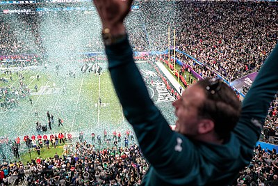 An Eagles fan in attendance at U.S. Bank Stadium celebrates following the team's victory at Super Bowl LII. An Eagles fan celebrates as confetti falls on the field at Super Bowl 2018, Minneapolis MN (40074198602).jpg