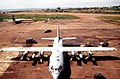 An overhead front view of a US Air Force C-130 aircraft is loaded ith supplies at the Entebbe International Airport. Trucks and other aircraft are in the background - DPLA - 424b98d92b8e1f858cb816deaa4a5c56.jpeg