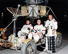 Three astronauts in space suits without helmets; two sit in a lunar rover mockup