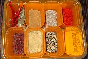 Bangladeshi cuisine - Typical spices used in a Bangladeshi household. Clockwise from top left, dried red chili pepper, bay leaves, cumin powder, cumin, red chili powder, turmeric powder, pãch poron, coriander powder and mustard.
