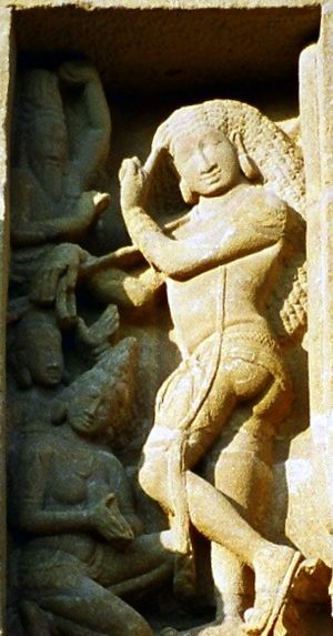 Bhikshatana - Bhikshtana, Kailashanatha temple, Kanchipuram. The young, nude Bhikshatana (right) holding a staff and with unwound hair is worshipped by women, who are seduced by him. An agitated sage (top left) raises his hand to hit Bhikshatana.