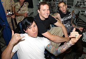 Kiri ke kanan: Tom DeLonge, Mark Hoppus dan Travis Barker mengunjungi AL Amerika Serikat yang berlabuh di Manama, Bahrain pada Agustus 2003