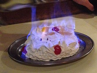 Flambé - A Bombe Alaska at a restaurant in Singapore which has been flambéed with alcohol