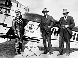 "Three men, two in suits and hats, the other in flying gear, standing in front of biplane bearing the legend ""Royal Air Mail"""