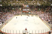 "The view of an ice hockey rink from behind and above one goal. Most players, dressed in either red and white or blue and black, are in the far right corner of the rink. Above center ice an electronic scoreboard reads ""9:09"" in green; under that, red numbers read from left to right ""0"", ""1"", and ""0"". The ""1"" is smaller than the two ""0""s. On the visible end of the rink, a red sign reads in black and white text ""Pizza Hut""."