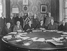 Six white men sitting around a conference table, with five more standing behind them. One of the seated men, third from the left, is sitting in a much more ornate chair than the others; he is the Prime Minister of Canada, William Lyon MacKenzie King.