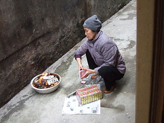 Joss paper - Woman burning joss papers in front of her house in Hanoi after having offered food to her ancestors