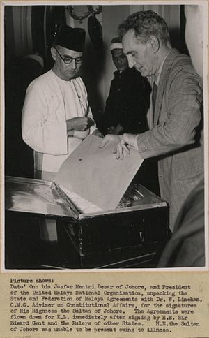 Federation of Malaya - Dato' Onn bin Jaafar Mentri Besar of Johor, and President of the United Malays National Organisation, unpacking the State and Federation of Malaya Agreements with Dr. W. Linehan, C.M.G. Adviser on Constitutional Affairs, for the signatures of His Highness the Sultan of Johor, 1948.