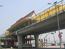 An elevated train station with a red and yellow pagoda-style roof.